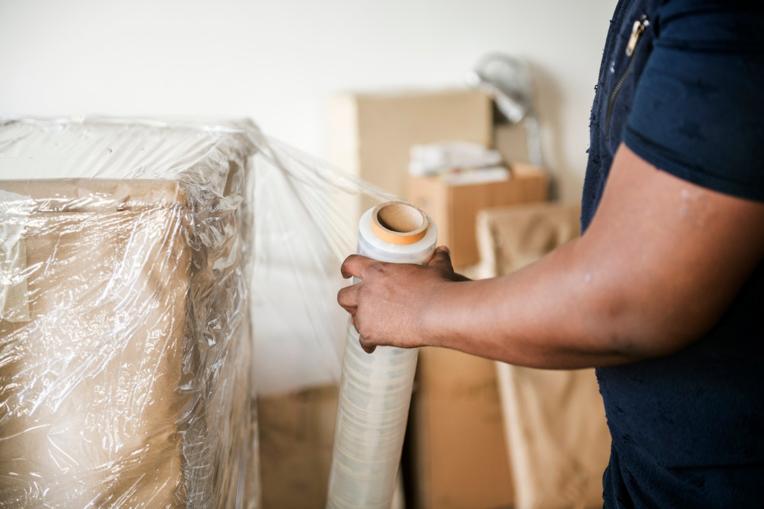 Mann pakker inn esker i plast. 10 tips for å gjøre flyttingen mer effektiv.